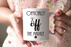 "Such a cute way to announce your engagement with this fun mug! Officially off the market! Perfect for any bride to be! All of our mugs are: - Dishwasher & microwave safe - Standard 3.15"" x 3.15"" white"