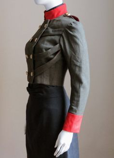 Very nice fitted military style jacket made from an olive green wool suiting and accented in bright red. Cropped to just above the waist with full length sleeves, gold buttons, a red stand collar and cuffs by Calicoandsteels on etsy.