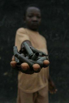 """Child playing with bullet casings, Democratic Republic of Congo. While there, seeing child soldiers, seeing children using mortars and bullet casings as toys, I was reminded of a quote of W.H. Auden: """"I and the public know; What all schoolchildren learn; Those to whom evil is done; Do evil in return."""""""