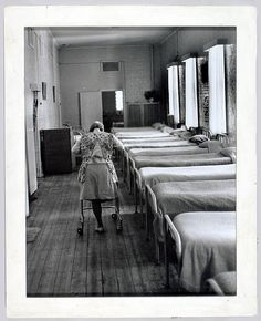 Mayday Hills Hospital (formerly Beechworth Lunatic Asylum) showing an interior, including a row of beds, close together, with a patients wearing an apron and using a walking frame. The patient, who has only one leg, is walking away from the camera.
