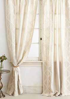 Appliqued Lace Curtain layered with dark tan velvet curtains over it to block light.
