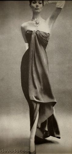 1960  Draping sweeps the shoulder and - with the first step - cascades into a floating panel that reveals the knee. In deep purple satin chiffon by Balenciaga.