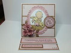 (Ref:H53) 15cm x 15cm easel card. Main image LOTV stamp 'Baby with Bunny', coloured with Promarkers and decoupaged. Papers Nitwit download 'Fine Linen'. Dies used, Spellbinders 'Floral Ovals', La La Land 'Berry Flourish', Die-namics 'Rolled Daisy', Marianne 'Rolled Roses' and Martha Stewart flower punch. Gems from internet search.