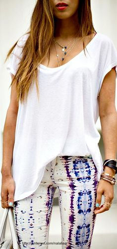 La camiseta es sencillo blance, y los pantelones eres azul, morado, y blanco estampado.