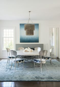 Pale blue tones are introduced in the dining room with a rug by Rosemary Hallgarten and art by Alex Weinstein | archdigest.com