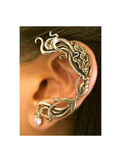 This detailed, antique bronze, Wave Rider Mermaid flows gracefully along the perimeter of the ear. It is available for the left ear only. (Diamond not included.) Our ear wraps require no piercings. The ear wraps have a sturdy wire that wraps behind the ear similar to a Blue Tooth headset. Our bronze ear cuffs are antiqued lightly, and bronze will tarnish, or patina over time. To maintain the golden color, clean with Mrs. Wright's Silver Cream and rinse with water. Do not dip in liquid anti…