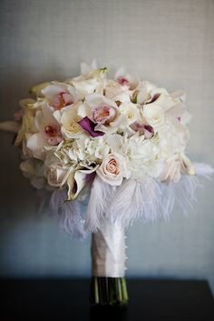 This vintage bouquet has roses, hydrangea, cymbidium orchids and mini calla lilies. Feathers are the dernier cri this season! www.flowermuse.com