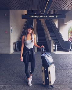 Jessica ricks wears a simple grey vest with black leggings, a matching black cap, and white converse sneakers to create this comfortable travel style. Airport Style Travel Outfits, Travel Outfit Summer, Vacation Outfits, Travel Style, Traveling Outfits, Travel Fashion, Summer Airport Outfit, Comfy Airport Outfit, Airport Fashion
