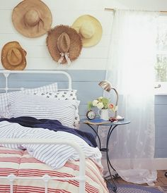 Coastal bedroom with straw hats on wall