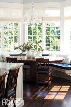 Shaped bench in bay window. A breakfast area combines deep woods with the kitchen's ever-present white.