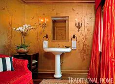 This home's Asian motif gets a glamorous twist in the powder room, where gold walls are painted with a bamboo design and bright red fabrics stand out - Traditional Home® / Photo: Edmund Barr / Design: Gail Plechaty