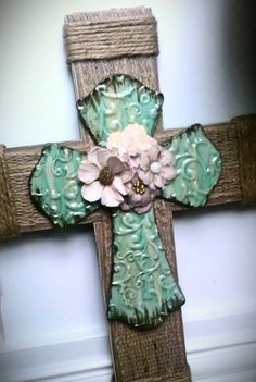 "Burlap Wooden Cross with Turquoise Cross.  The largest cross is 16"" H, with a burlap overlay. Each edge is wraped with burlpap rope for decoration. Mounted on that is a turquoise cross topped off with some small prima flowers - making it look very 'feminine'."