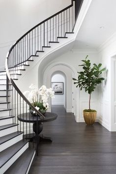 Chic, classic foyer features a curved staircase wall filled with a black round table and orchids. Chic, classic foyer features a curved staircase wall filled with a black round table and orchids. Black Stair Railing, Black Stairs, Curved Staircase, Staircase Design, Staircase Ideas, White Staircase, Grand Staircase, Spiral Staircases, Staircase Handrail