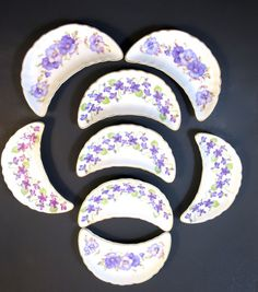 8 Bone Dishes Porcelain Purple Flowers Pansies Violets Fine China Tableware  Scallops shaped bone plates  Fine porcelain tableware  5 Bone Plates w/ Violets  3 Bone Plates w/ Pansies   Marked Andrea by Sadek #7753 All have the same #, a set  Made in Japan Dates from the 1960s  Original Stickers   Size: 6.5 x 3 inches Condition: Excellent; appear  unused; no chips or cracks.