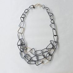 Gold Shape Statement Necklace by Kendra Renee. This necklace refuses to stand in line. Each link is a unique, hand-forged shape with a rustic texture and combines with the others to encircle your neck in a lively tangle. Solid 14K links are sprinkled in at random to add an extra element of playful luxury. Hook the clasp on anywhere to adjust the length. Hand-forged in sterling silver and 14K gold.