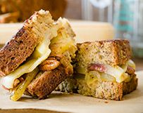 Hummingbird Grilled Cheese 1 (1/2-inch thick) fresh pineapple ring 1 tablespoon butter, softened 2 slices banana bread (homemade or store-bought) 7 pecan halves 2 teaspoons honey 2 ounces (1/2) cup) Wisconsin Fontina Cheese, sliced or shredded