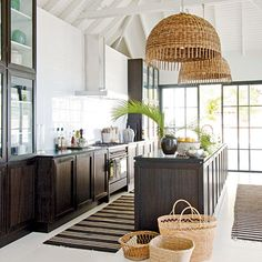 Statement-making wicker Italian lamps add coastal style and creativity to the kitchen. Glass-front cabinets keep the black mahogany from looking too dark, and the white-painted interior makes everyday dishes look like art. Handwoven baskets weave a natural element into the decorating scheme and speak to an island way of life.