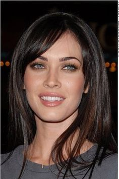 """This look is really cute as Megan Fox has her straight long hair styled around her face. Her hair falls evenly at the sides leaving bangs to be swept at the forehead.<span id=""""desc_split""""></span>This haircut is long.<span id=""""desc_split""""></span>The hair colouring is dark brown."""