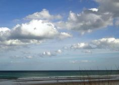 Beautiful sky, sparkling water, white sand and sea oats