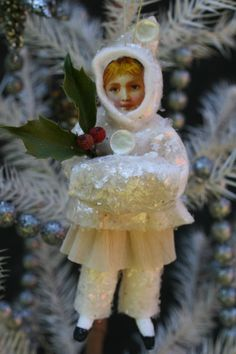 Spun Cotton ornament with lithographed paper face, cotton batting clothes, antique buttons and mica flakes.