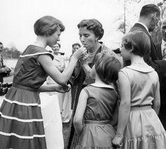Princess Margrethe of Denmark helps her mother Queen Ingrid lighting a cigarette.