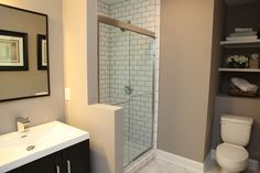 Master bathroom Functional Gray by Sherwin Williams. Ducts are behind the toilet which left a huge empty space above. We turned it into storage.