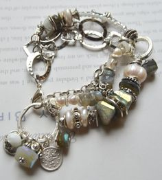 a true artisan- bold beauty! -this has three strands in the front- a strand of rolo link chain, a strand made up of pearls, wavy spacers, stacks of this reflective labradorite, to a center of studded silver beads, then a main strand of stacked mobious beads, to large luminous pearls, wavy spacers, studded silver beads, a wheel of expensive reflected faceted of labradorite, expensive artisan studded wheels, new nuggets of expensive AB mystic treated faceted nugget of labradorite -to wavy…
