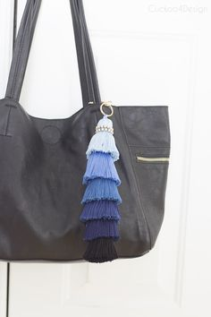 large blue ombre tassel on a black purse
