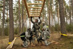 U.S. Army Soldiers with 615th Military Police (MP) Company, 709th MP Battalion, get over an obstacle on the Rugged Terrain Trail (RTT) in Grafenwoehr, Germany, March 26, 2013. The RTT combines foot marching with obstacles and rapid elevation changes and is designed to replicate terrain in the current operating environment.