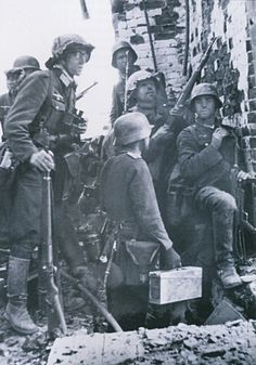 Three photographs taken in sequence showing a officer(wearing glasses)with his infantry assault group sheltering behind a factory building wall in northern part of the city of Stalingrad.