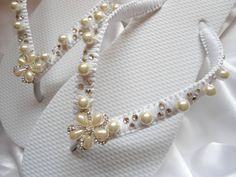 Beautiful white flat bridal flip flops macramé wrapped with white satin and adorned with crystals, pearls, and a gorgeous rhinestone flower