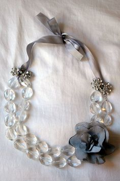 DIY necklace - fold an inexpensive beaded necklace in half...attach ribbon to both ends...add clip earrings to hide the knots...add fabric flower pin