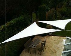 Une terrasse à l'abri du soleil avec deux voiles d'ombre en triangle fixées aux murs