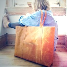 Huge leather tote. Am I the only one who thinks the weight of the bag pulled the model down? Or maybe she's living inside it? Still a hot bag.