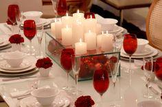 ) Esta é a solução montada por Marlene Peccin, em Gramado, na Sergio Bertti. Observe a caixa com bolas dentro que vira a base das velas. E, para cada lugar à mesa, um vasinho de flor. Tudo em vermelho e branco.