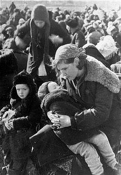 A young mother and her children wait to be executed near Lubny on Oct. 16, 1941.  Though the sound of shots must have been audible to those waiting, none are crying or behaving with anything other than incredible dignity, faith, and resolve.  To answer why so many didn't just overwhelm their captors, it is well-known that a few men with guns can easily control crowds many times larger; especially if the crowds are of women, children and the elderly.