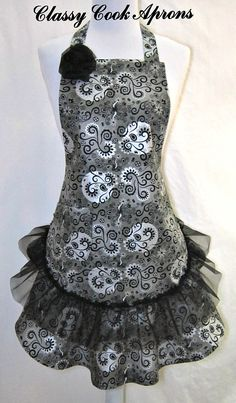 This full apron is in a stunning Haute Couture special occasion designer fabric featuring a stylized floral swirl motif in Black, Silver and 8 Shades of Grey. For a touch of elegance, we added a Sheer Black Organdy ruffle above the matching flounce. Then to top it off, we added a lined right hand pocket, and a big beautiful black organdy rosette at right bib corner. And Voilà! OMG Gorgeous! Serve up your own evening soirée in this one-of-a-kind Glamor Girl party accessory!