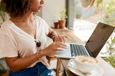 Young woman working on laptop in cafe by jacoblund. Cropped image of young woman working on laptop while sitting in cafe. African girl using laptop computer with a cup o. Marca Personal, Personal Branding, Personal Finance, Laptop Photography, Photography Tips, Corporate Photography, Photography Branding, Product Photography, How To Start A Blog