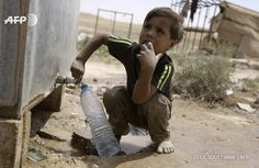 Syria, Al-Hawl : An Iraqi child who fled with his family the northern province of Nineveh following the advance of jihadists of the Islamic State (IS) group, fills a bottle with water in a refugee camp in al-Hawl located some 14 kilometers from the...