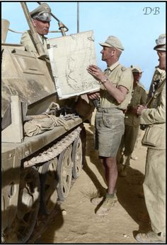 "General Erwin Rommel looking at a map with Oberst Eduard Crasemann, commander of the 15th Panzer Division and other officers in the Gazala area of North Africa, May 1942.   Rommel is in his Schützenpanzer Befehlsfahrzeug Sd.Kfz 250/3 (""Greif""), a light armoured halftrack.  The map appears to be a captured or abandoned Allied Army copy, according to some of the notes written on the right hand side - ""Mortar - Bn.HQ. - Coy - Bde."""