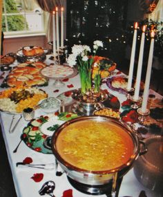 Finger food buffet with warm mexican dip in the foreground, veggie trays, cheeses, ham rolls, and more!