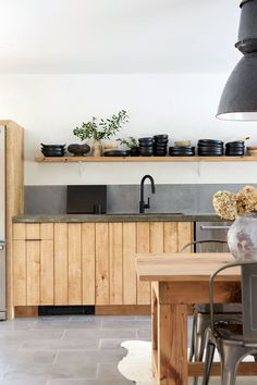 Concrete countertop and vertical paneled modern cabinets. Dining table in the kitchen. #rusticmodern #rustickitchen #floatingshelves #concretecountertops
