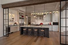 Incredible kitchen framed by steel framed window panes suspended from a reclaimed ceiling beam over beautiful reclaimed wood floors.