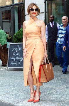 How Jennifer Lopez does monochromatic dressing—the orange undertones in her peachy sleeveless midi dress, coral accents in her lip color, tote and shoes present uniformity and add subtle yet crucialcontrastto the outfit as a whole. Recreate her sophisticated day-to-night look with under-$100 picks.