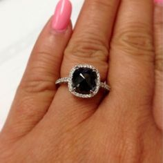 A single rose cut 2 1/4ct #blackdiamond sits surrounded by a halo of sparkling white diamonds in this unique 14k white gold ring. This gorgeous ring is set with seventy sparkling white diamonds totaling 3/8ct total weight. Coby Madison Jewelry has the most exquisite collection of black diamond engagement rings online! #blackdiamondring #blackdiamondengagementring