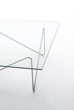 TESEO design Lorenzo Arosio | Series of low tables with top in 8 mm thick tempered glass. The slender supporting structure is made by a brushed and bent steel rod.