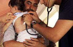 A Syrian father watches as Turkish medical staff examine his child who has developed breathing difficulties. © UNHCR/A.Branthwaite