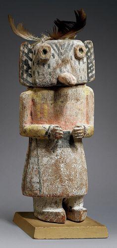 """KACHINA MONGWU Cette poupée Mongwu représente le Grand Hibou à Cornes. Barton Wright (Esprit Kachina, Galerie Flak, Paris, 2003) identifie cette poupée à l'aide du triangle dessiné entre les deux yeux. D'après lui, """"ces kachinas agissent en tant que guerriers contre les clowns."""" Hauteur: 22,5 cm."""