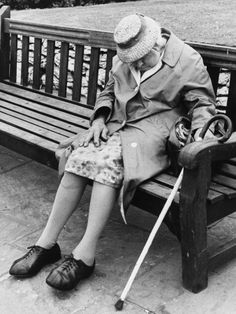 An elderly lady soundly asleep on a park bench in Manchester-photograph-by Shirley Baker