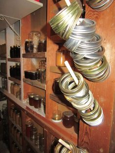 """""""Vertical Storage for Canning Jar Rings""""  With a few wooden dowels and some vertical storage space, you can store canning jar bands in an easy-to-access and convenient way. From MOTHER EARTH NEWS"""